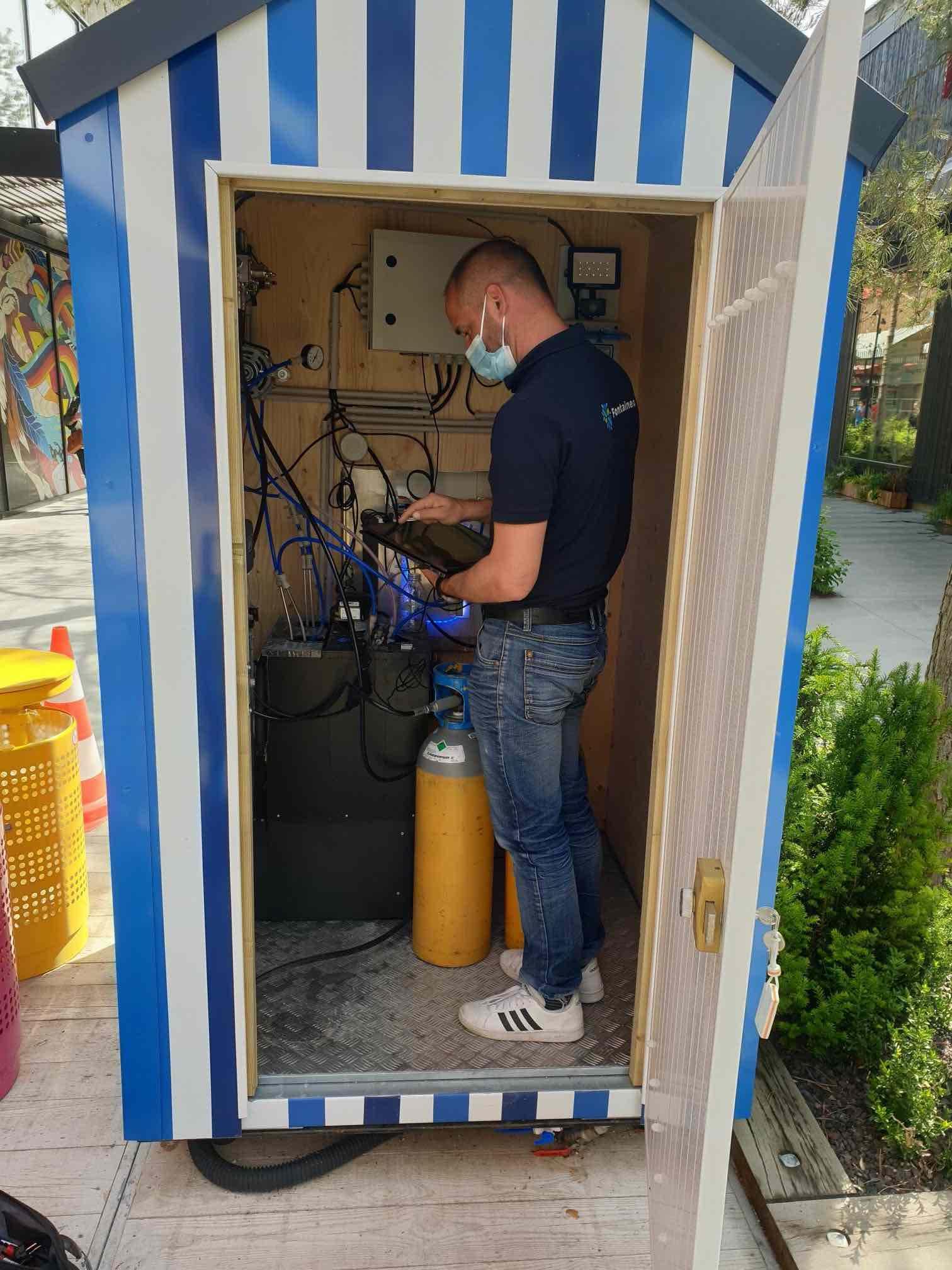 Technicien Fontaineo en train de vérifier une fontaine dans le cadre d'une installation de fontaine à eau